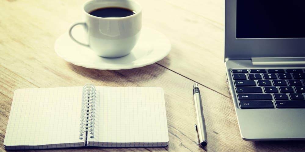 Бележник, химикал, кафе и лаптоп