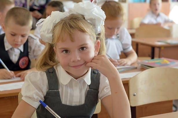дете с панделка седи на бюро