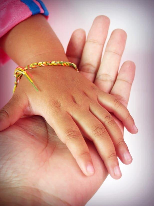 детска ръка върху ръка на възрастен