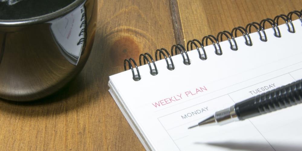 Календар с ъс седмичен план и чаша кафе